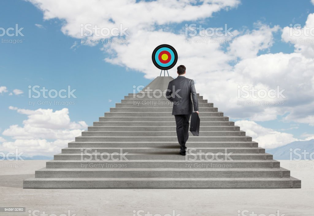 Businessman Climbing Stairs To Reach Target At Top stock photo
