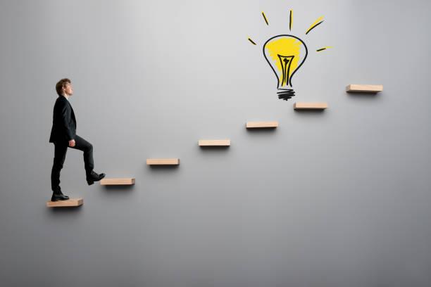 Businessman climbing steps towards light bulb stock photo