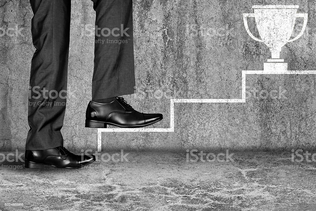 Businessman climbing up to get Award stock photo