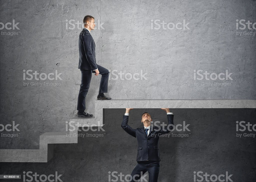 Businessman climbs the concrete stairs, which the other person keeps. stock photo