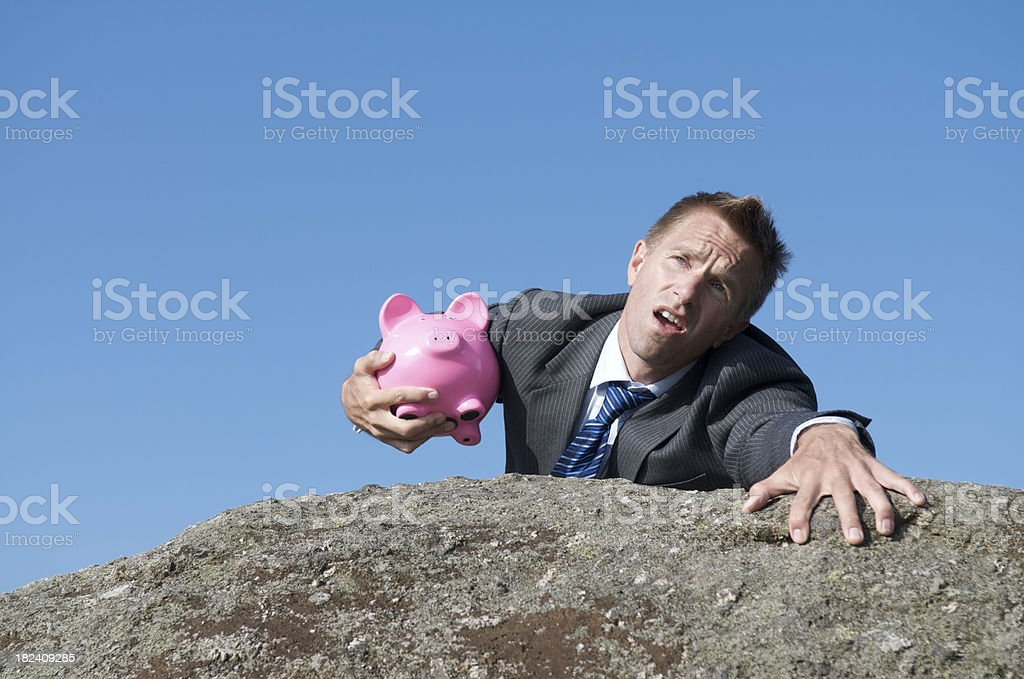 Businessman Clinging to Fiscal Cliff with Piggy Bank stock photo