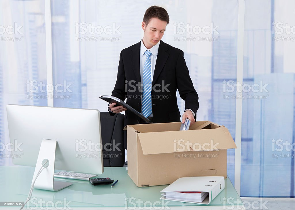 Businessman Collecting Office Supply In Cardboard Box At Desk stock photo