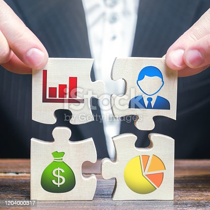 istock A businessman collects puzzles symbolizing individual elements and attributes of doing business. Project management. Good planning, Organization of the process, the creation of a business model. 1204000317