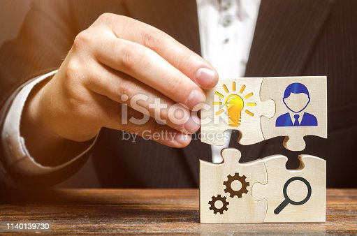 istock Businessman collects puzzles with the image of the attributes of doing business. Strategy planning concept. Organization of the process. Creating a business model. Management. Research, marketing. 1140139730