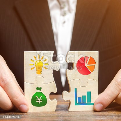 istock Businessman collects puzzles with the image of the attributes of doing business. Strategy planning concept. Organization of the process. Creating a business model. Management. Research, marketing. 1140139732