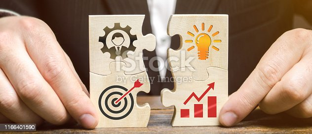 istock Businessman collects puzzles with the image of the attributes of doing business. Strategy planning concept. Organization of the process. Creating a business model. Management. Research, marketing. 1166401590