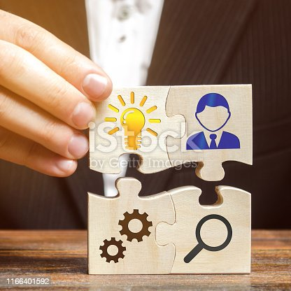 istock Businessman collects puzzles with the image of the attributes of doing business. Strategy planning concept. Organization of the process. Creating a business model. Management. Research, marketing. 1166401592