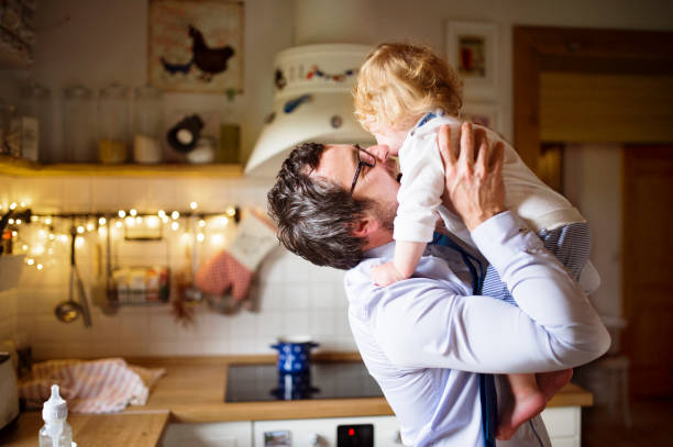 Businessman coming home from work, kissing his little son. stock photo