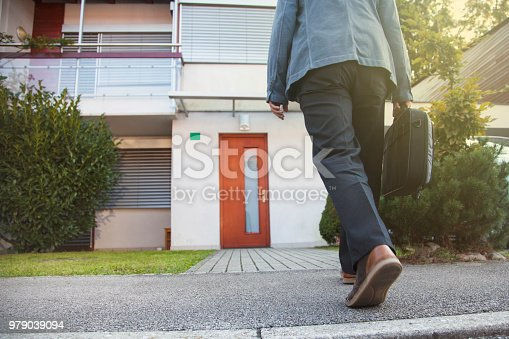 Man  in front of his house with bag. Going to the door. Coming home.