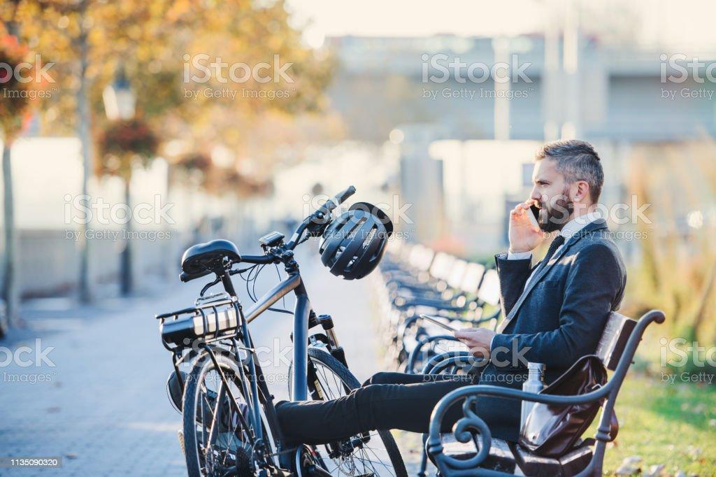 Geschäftsmann Pendler mit Fahrrad auf Bank in der Stadt sitzen und telefonieren. - Lizenzfrei Abenddämmerung Stock-Foto