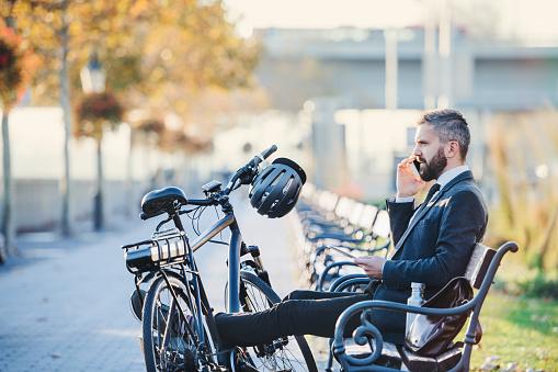 Geschäftsmann Pendler Mit Fahrrad Auf Bank In Der Stadt Sitzen Und Telefonieren Stockfoto und mehr Bilder von Abenddämmerung