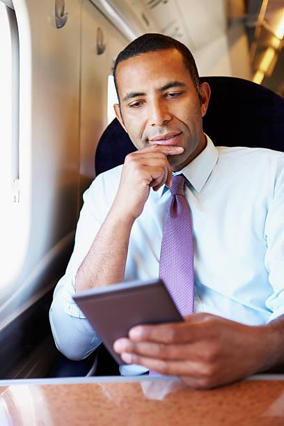 geschäftsmann pendeln auf zug lesen e-book - schnell lesen lernen stock-fotos und bilder