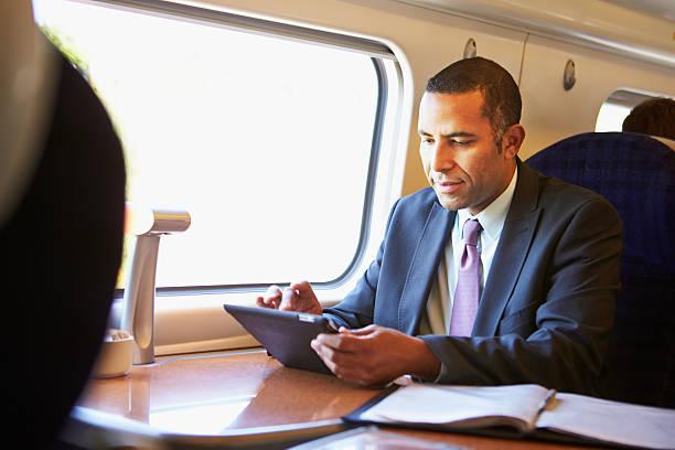 geschäftsmann pendeln mit tablet pc auf den zug - schnell lesen lernen stock-fotos und bilder