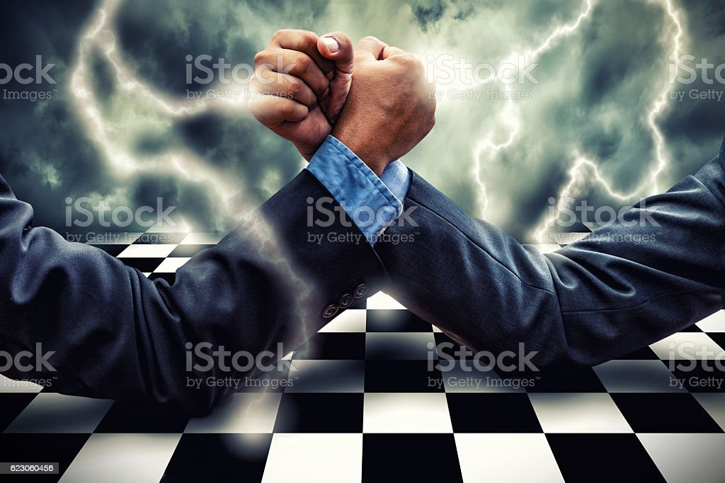 Businessman Competing In Arm Wrestling on lightning storm effect stock photo