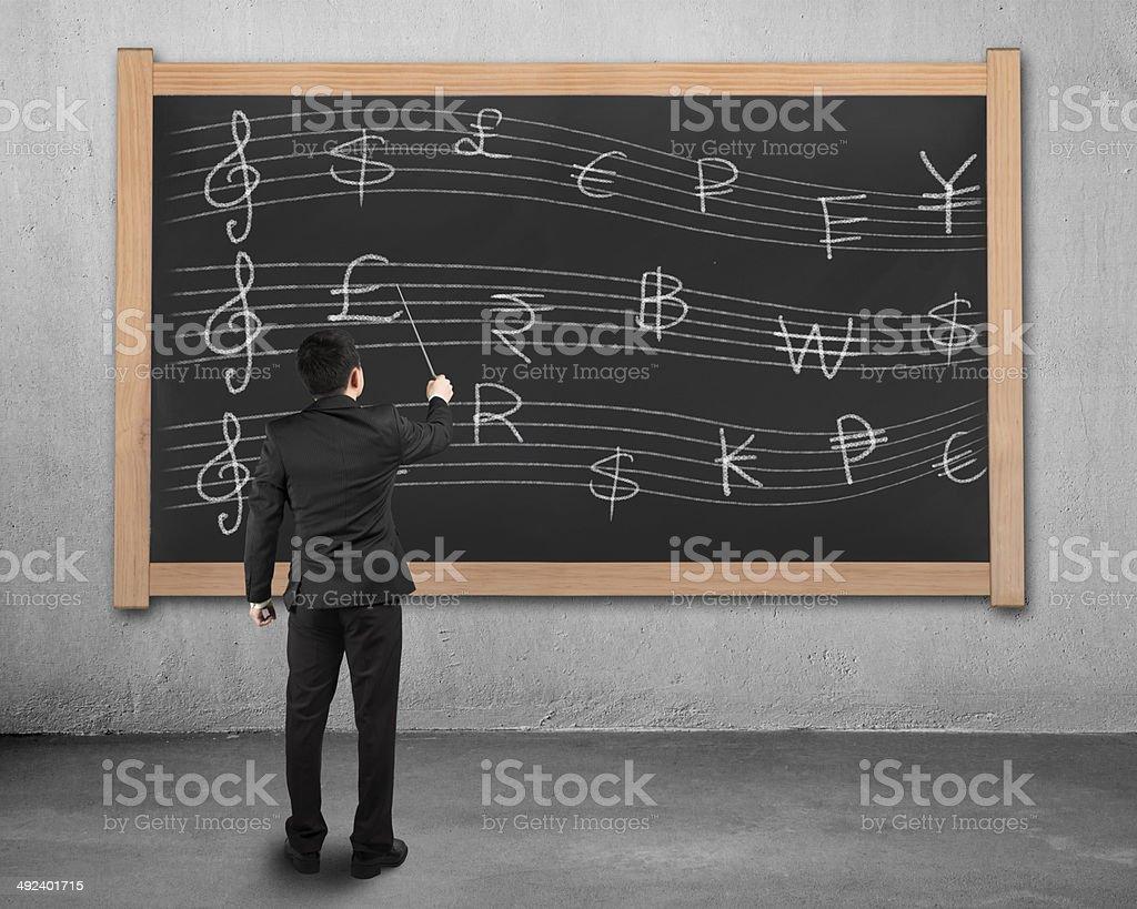 Businessman conducting with money symbols stave on blackboard royalty-free stock photo
