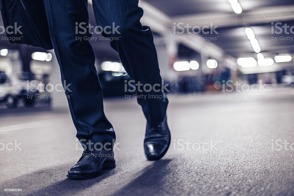 Businessman confidently walking at night stock photo
