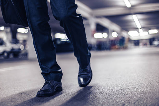Businessman confidently walking at night Businessman confidently walking at night stepping stock pictures, royalty-free photos & images