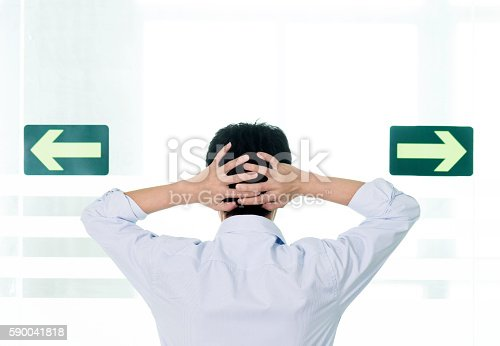 istock Businessman confused by the choice of green arrows pointing 590041818