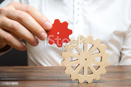istock Businessman connects a small red gear to a large gear wheel. Symbolism of establishing business processes and communication. Increase efficiency and productivity. The best business formula for success 1140416855