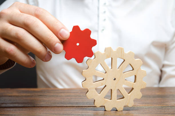 Businessman connects a small red gear to a large gear wheel. Symbolism of establishing business processes and communication. Increase efficiency and productivity. The best business formula for success stock photo