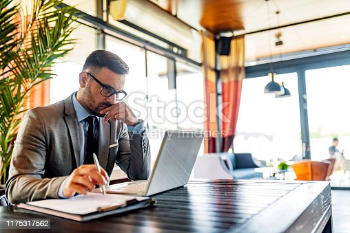Serious millennial man using laptop sitting at cafe table, focused guy in suit communicating online, writing emails, distantly working or studying on computer in public place.