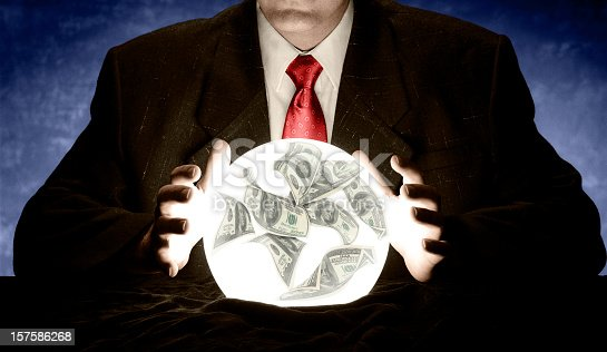 A businessman is consulting a crystal ball to foretell the future of the economy.  There are 100 dollar bills floating in the crystal ball. The businessman is wearing a suit with a red tie. There is a blue glow in the background. This is a studio shot with a canvas background.