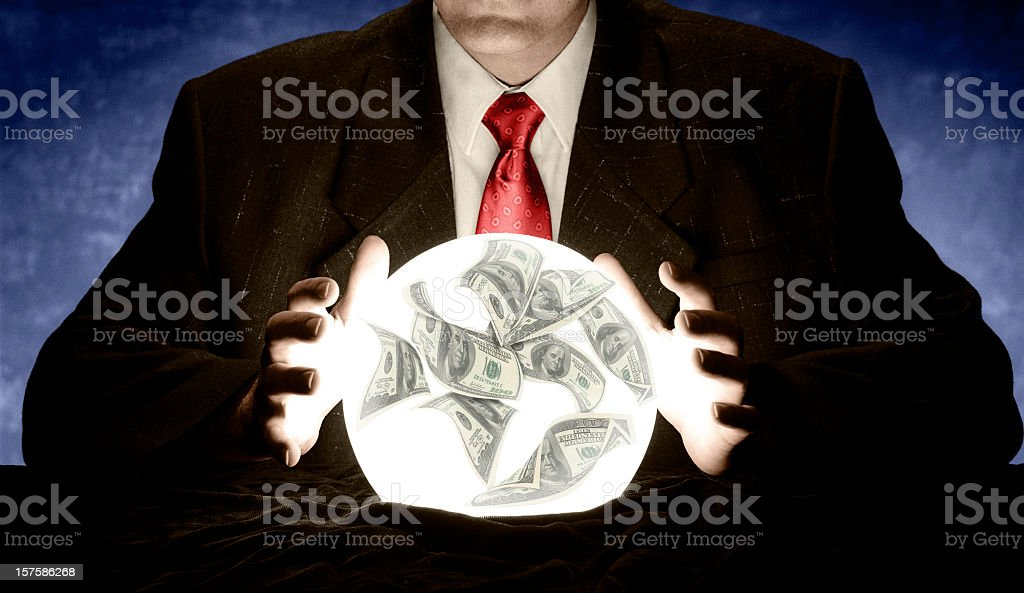 Businessman Consulting a Glowing Financial Crystal Ball stock photo