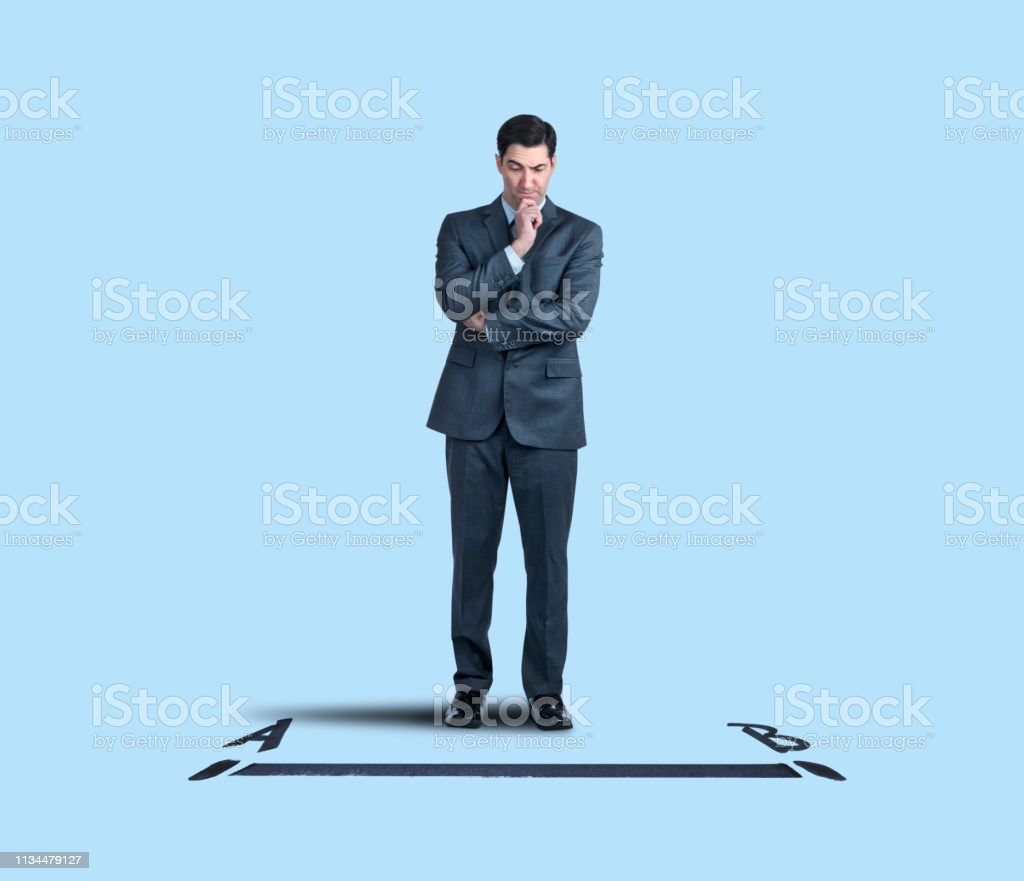 Businessman Contemplates The Shortest Distance Between Point A And Point B stock photo