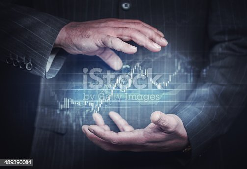 Businessman controlling financial charts. Stock photo.