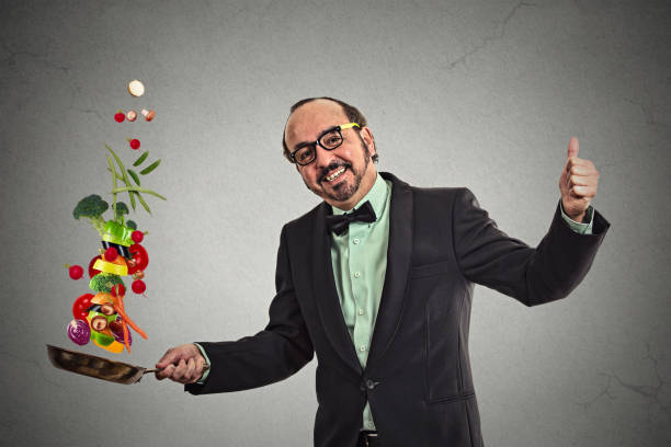 Businessman cooking vegetables with a pan showing thumbs up stock photo
