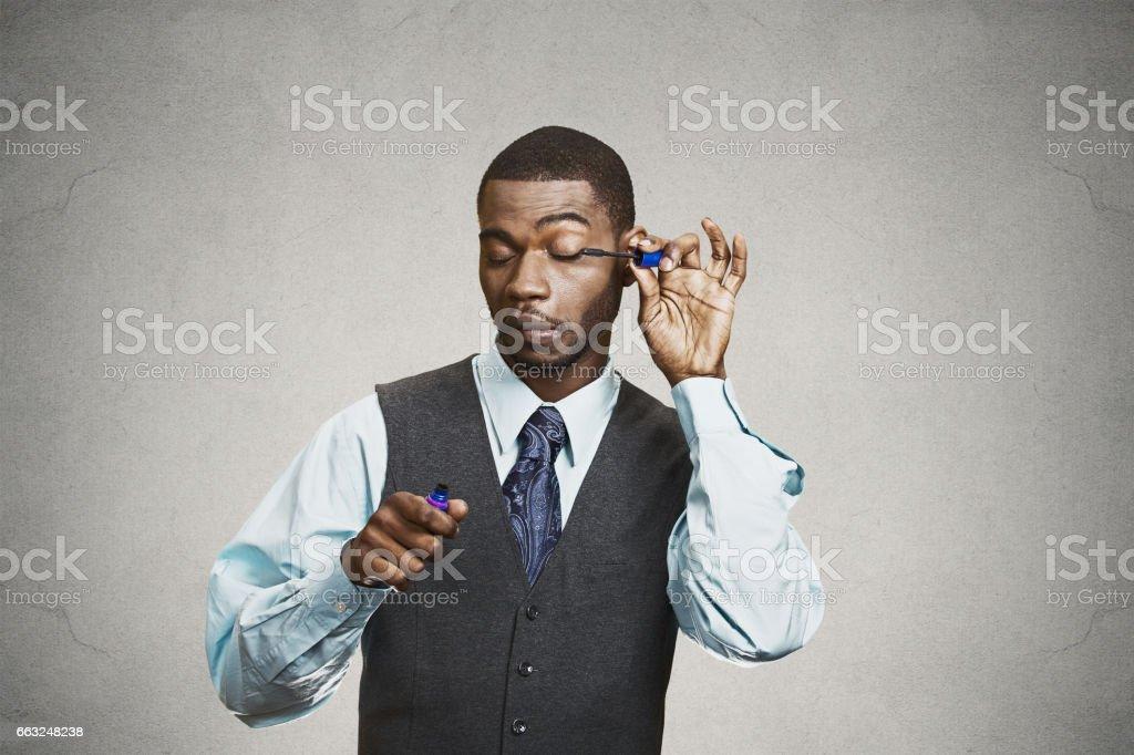 businessman, corporate executive applying make-up, eyelashes mascara stock photo