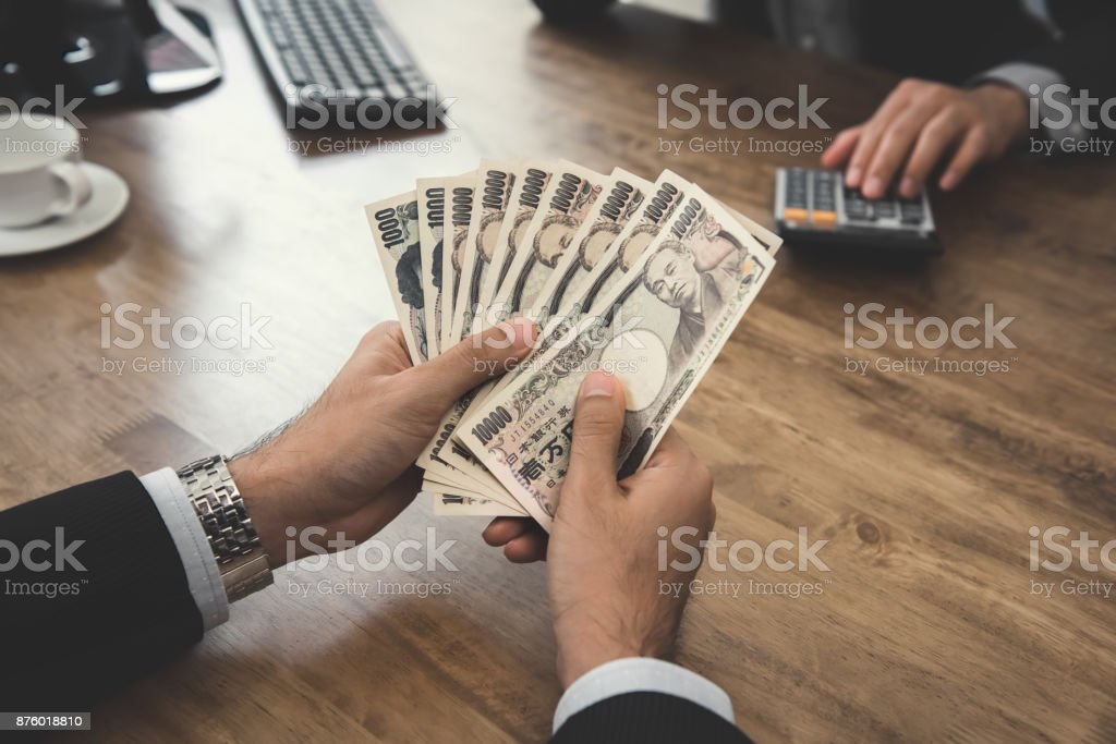 Businessman counting Japanese Yen money in an office stock photo