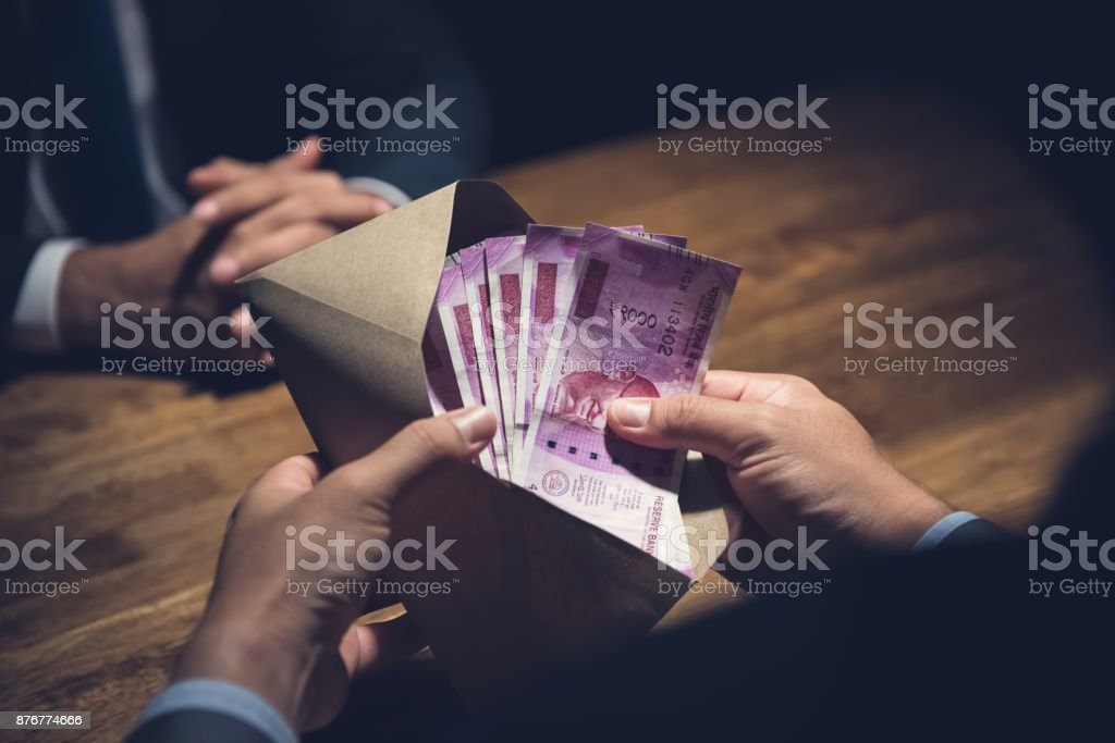 Businessman counting money, Indian Rupee currency, in the envelope just given by his partner after making an agreement in private dark room stock photo