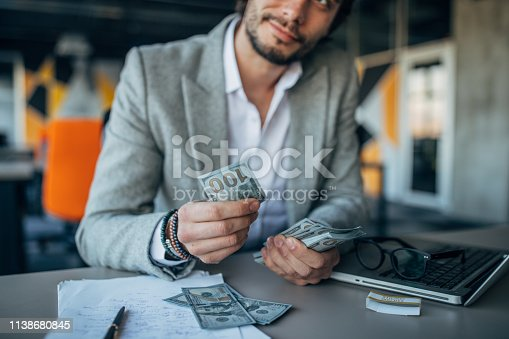 Handsome businessman working in the office and counting money