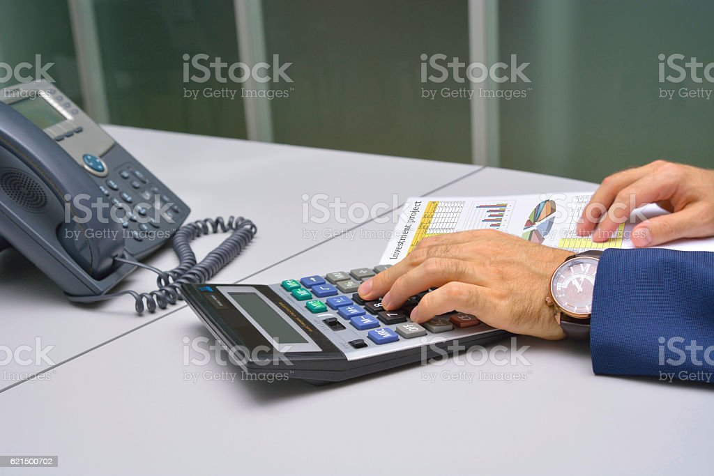 Businessman counting on calculator at the office photo libre de droits