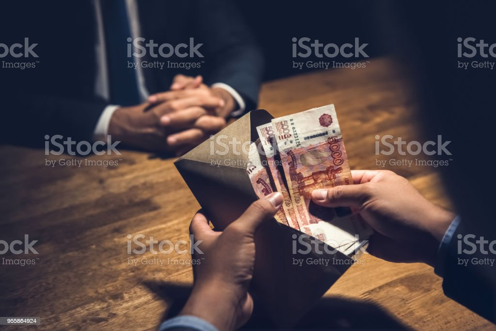 Businessman counting Russian ruble in brown money envelope stock photo