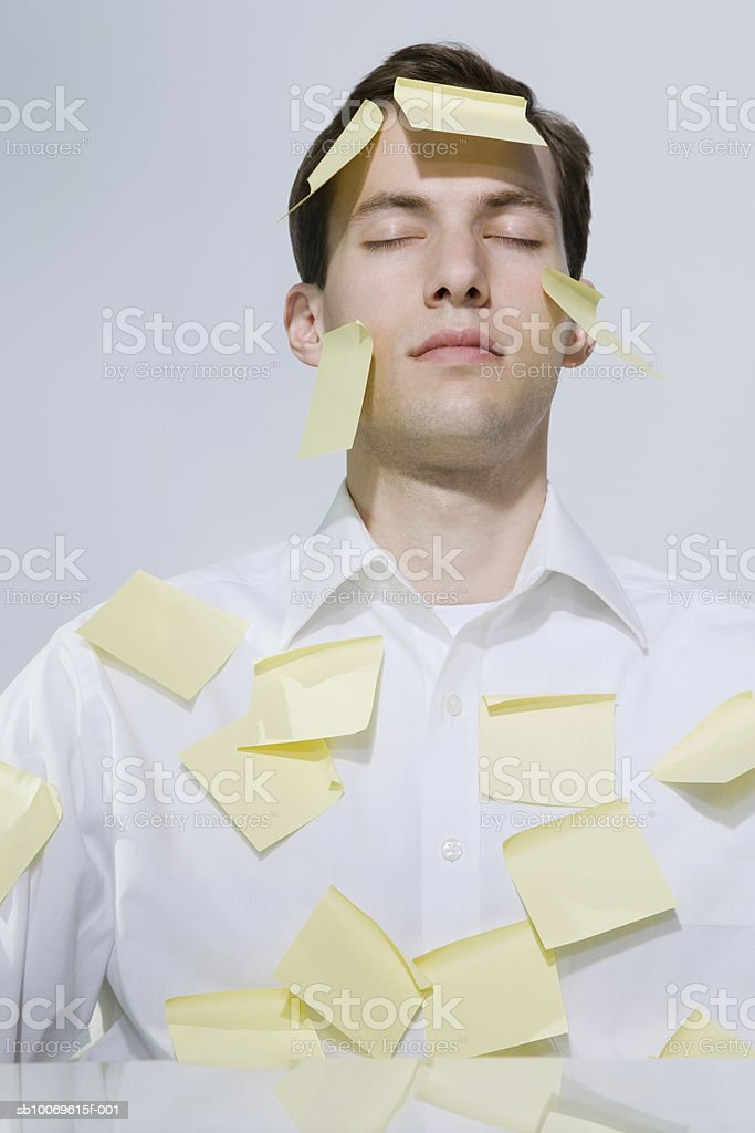 Businessman covered with adhesive notes, eyes closed foto de stock libre de derechos