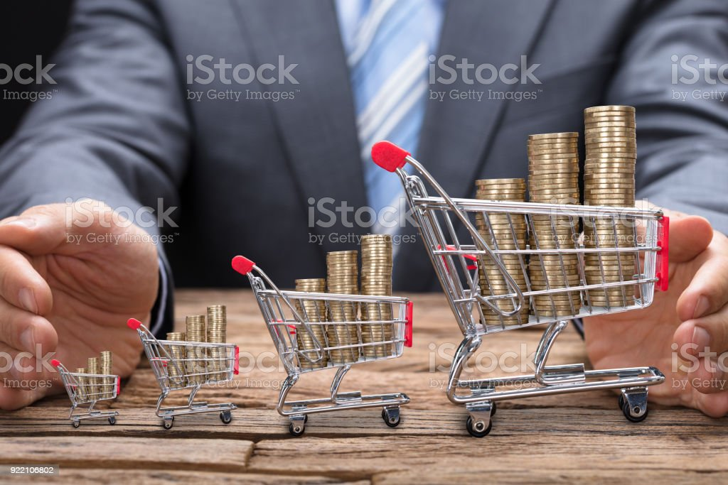 Businessman Covering Coins In Shopping Carts At Table stock photo