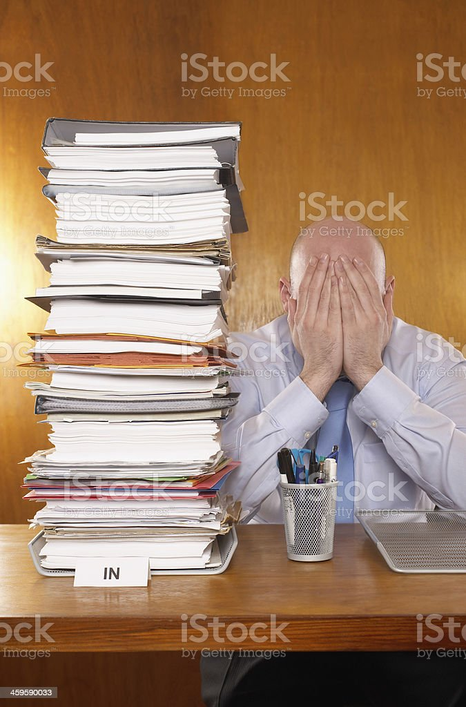 Businessman Covering Face With Hands By Stack Of Folders stock photo