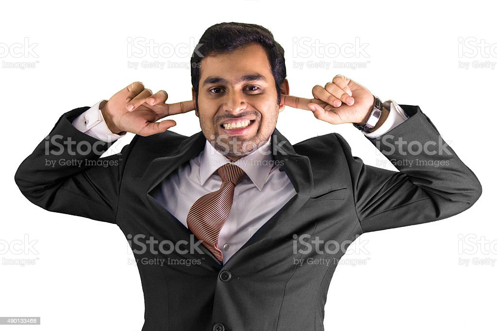 Businessman covering his ears with his fingers stock photo