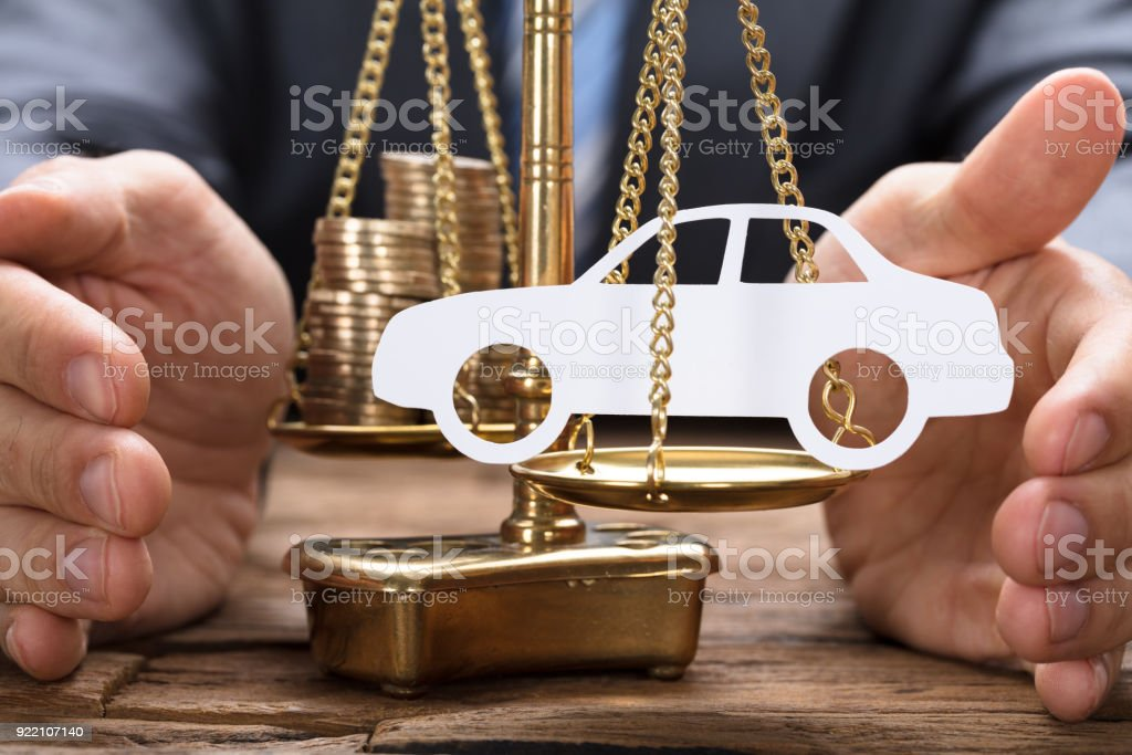 Businessman Covering Paper Car And Coins On Weighing Scale stock photo