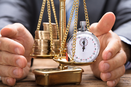 istock Businessman Covering Stopwatch And Coins On Weighing Scale 922107110
