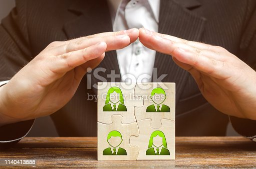 istock Businessman covers with hands the business team of employees. Patronage support, encouragement, privilege and financial aid. Government support smaller or local businesses. Team insurance, protection. 1140413888