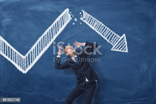 istock Businessman cowering on blue blackboard background with chalk drawing of 637822740