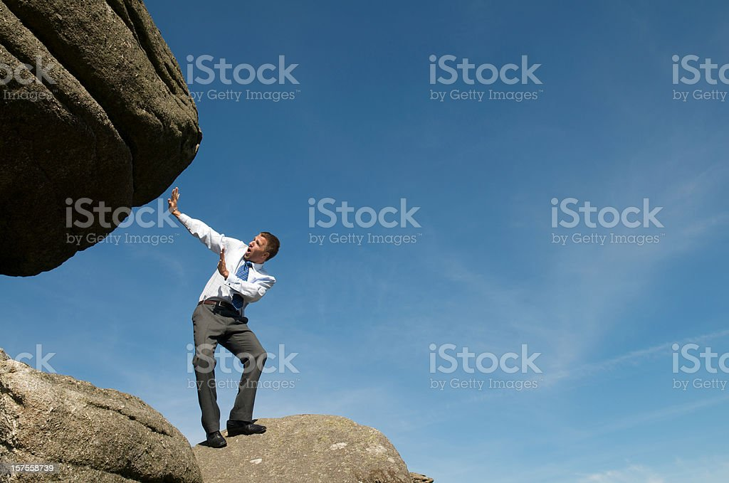 Businessman Cowers From Massive Falling Boulder stock photo
