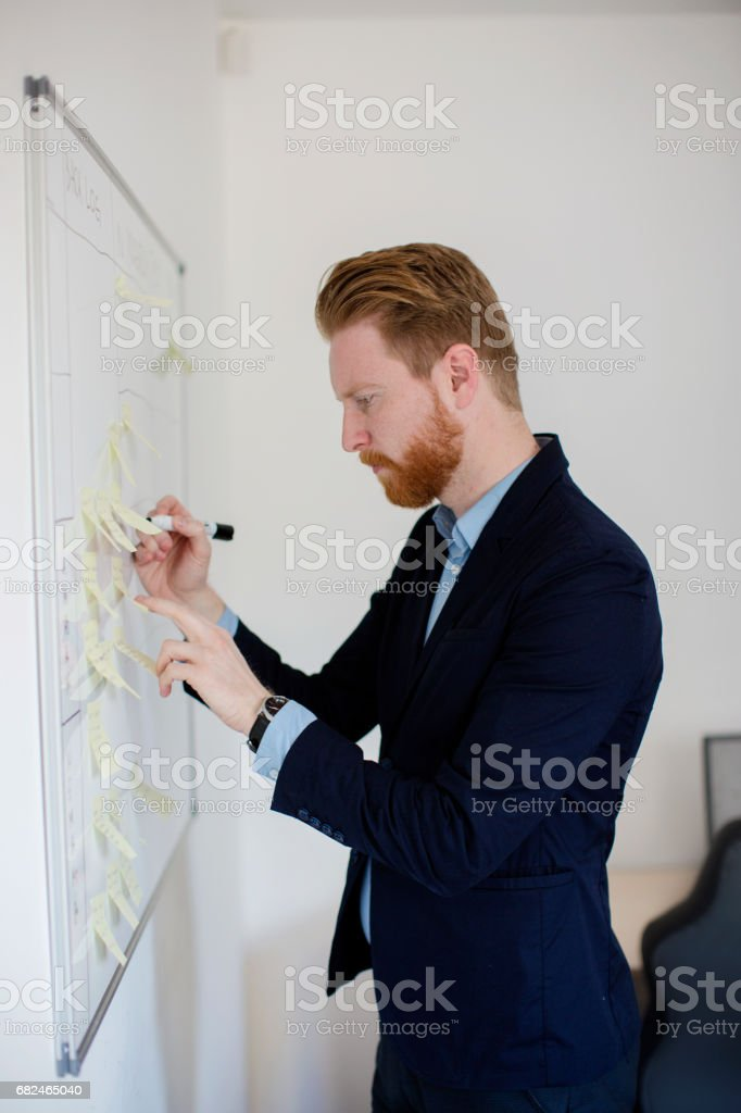 Businessman creating business strategy at white board royalty-free stock photo