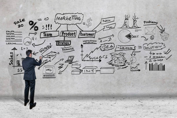 Businessman creating strategy on a wall stock photo