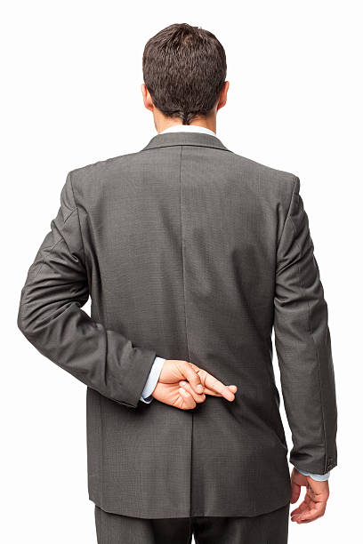 Businessman Crossing Fingers Behind His Back - Isolated stock photo