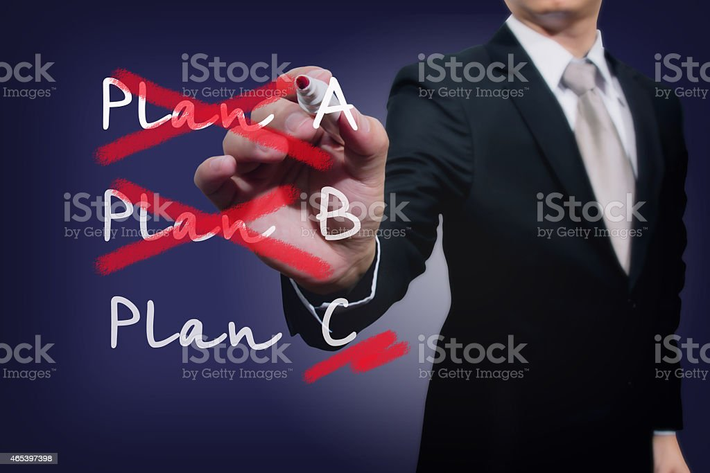 Businessman crossing our plans A and B leaving only plan C stock photo