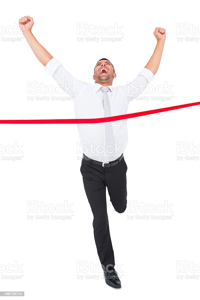 Businessman crossing the finish line stock photo